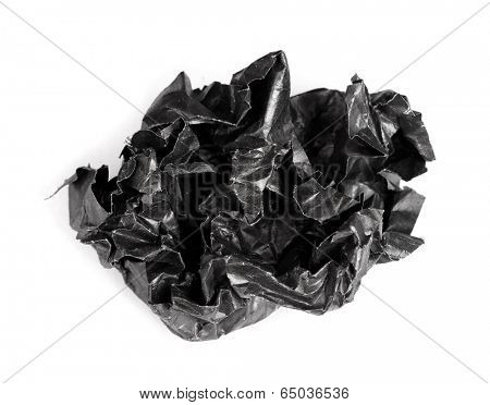 Screwed up piece of black paper isolated on white background
