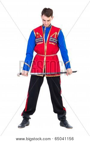 Russian cossack dance. Young dancer posing with sword