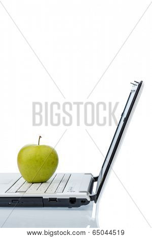 an apple is on the keyboard of a computer. symbolic photo for vitamin-rich and healthy snack.