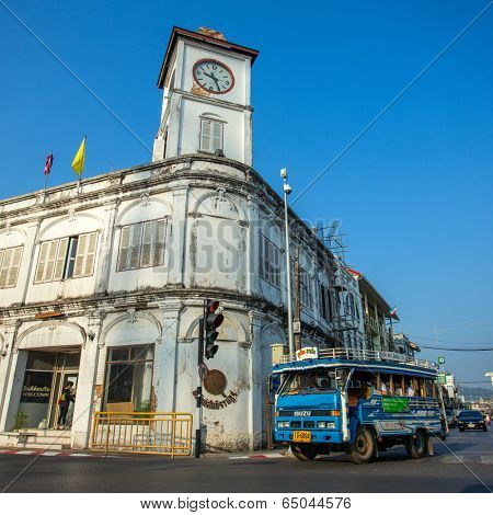 PHUKET TOWN, THAILAND - March 3: A songthaew, local bus passing by the Promthep Clock Tower on March 3, 2014. The Clock Tower was build in 1914.