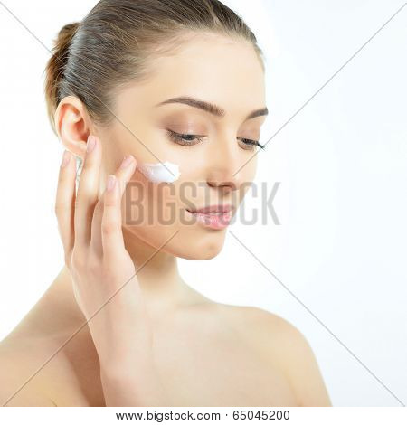 Beautiful young woman applying cream on her face. Girl with perfect skin over white.