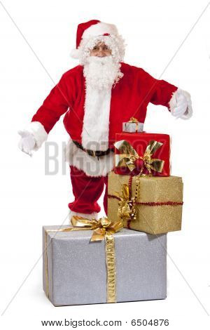 Santa Claus Standing Behind Christmas Gift Boxes Presents It With Open Arms