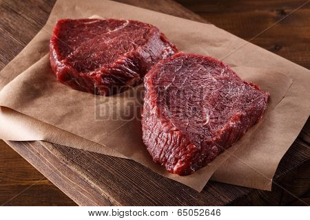 Succulent tender raw lean beef steaks lying on a sheet