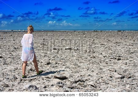 The girl goes on the coast from dead corals