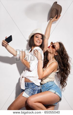 two young women taking picture of them selfs with mobile