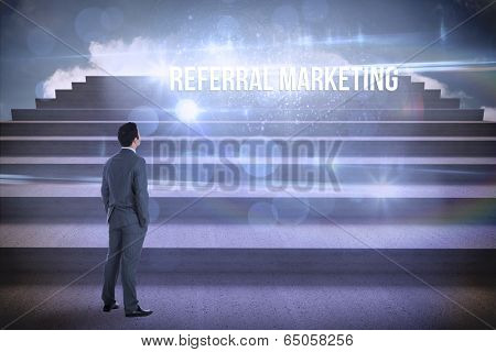 The word referral marketing and businessman standing against steps against blue sky