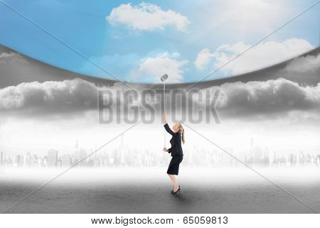 Composite image of businesswoman pulling down blue sky over city