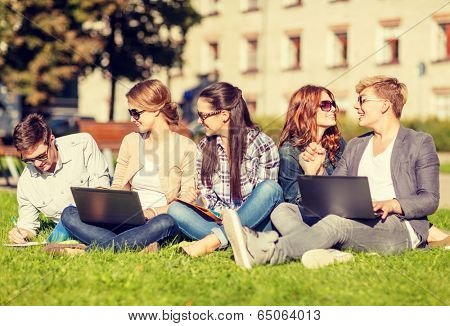summer, internet, education, technlogy and campus concept - group of students or teenagers with laptop, notebooks and folders