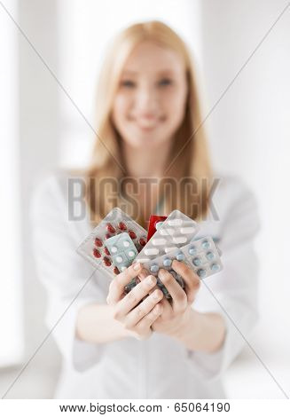 healthcare, medical and pharmacy concept - female doctor with packs of pills