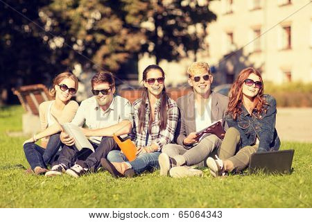 summer, internet, education, campus and teenage concept - group of students or teenagers with laptop, notebooks and folders