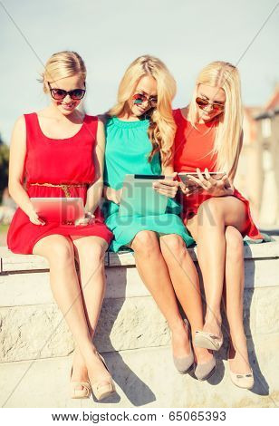 holidays and tourism concept - beautiful blonde girls toursits looking into tablet pcs in the city