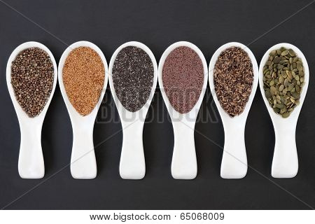 Seed food selection in porcelain scoops over slate background.