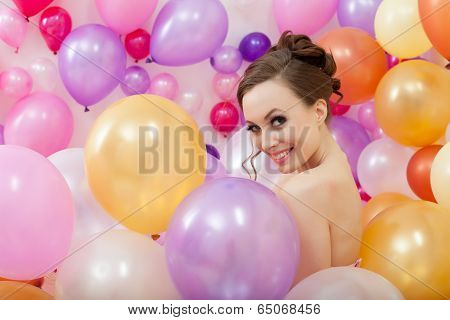 Smiling young woman posing with balloons