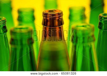 Ten empty beer bottles on a yellow background