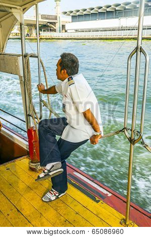 Captain Sitting On The Safety Chain Of The Ferry
