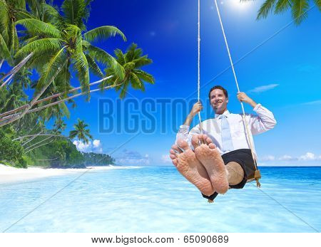 Businessman swinging at tropical beach.