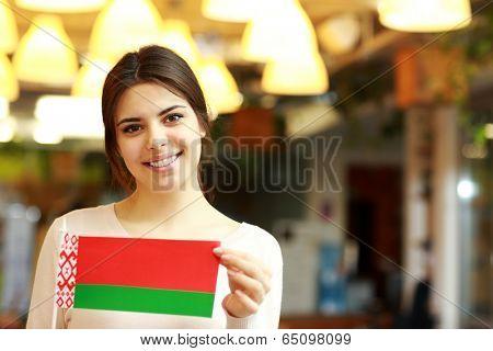 Happy female student holding flag of belarus