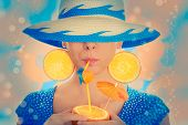stock photo of orange  - Young woman with orange slice earrings drinking from an orange - JPG