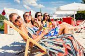 stock photo of sun-tanned  - Four woman lying on beach lounger - JPG
