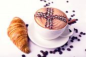stock photo of scum  - Cappuccino cup with drawing on scum and Croissant - JPG