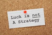 picture of reminder  - The phrase Luck is not a Strategy on a cork notice board as a reminder that your business or life plans cannot succeed on good fortune alone - JPG