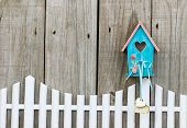 foto of bird fence  - Teal blue and pink birdhouse with wooden hearts hanging over white picket fence - JPG