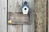 foto of log fence  - Blank rustic wood sign with blue and white birdhouse hanging on fence next to tree - JPG