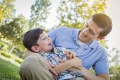 picture of tickling  - Loving Young Father Tickling Son in the Park - JPG