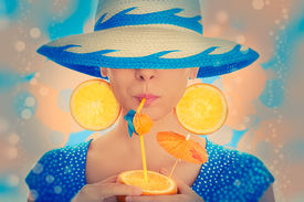 image of incognito  - Young woman with orange slice earrings drinking from an orange - JPG