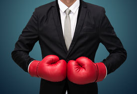 stock photo of knockout  - Businessman standing posture in boxing gloves isolated on over blue background - JPG
