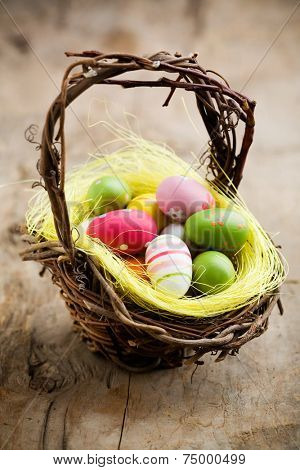 Colorful easter eggs in brown basket, shallow focus