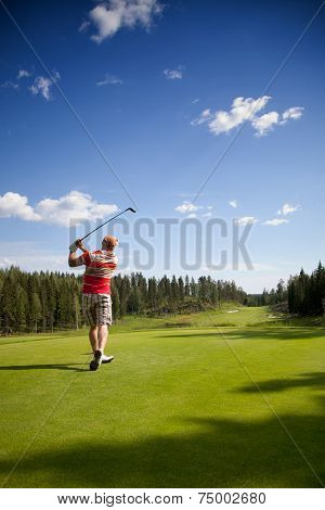 Male golfer shooting a golf ball