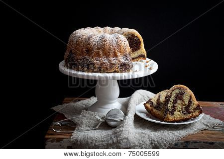 Marble bundt cake on wooden table, black background
