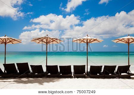Turquoise sea, deckchairs, white sand and beach umbrellas. Calmness and relaxation. Resort and spa.