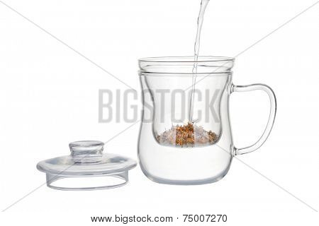 Preparation of the chamomile tea, pouring hot water into a Tea infuser with dry chamomile flowers isolated on white.