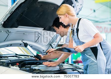 Male and female mechanic team examine car engine with light and checklist in workshop