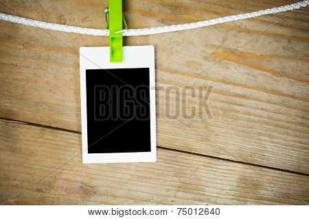 blank photos hanging on rope, wooden background
