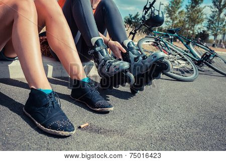 Two Women Sitting By Roadside Wearing Rollerblades