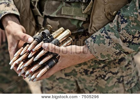 Military Personnel holding .50 Caliber BMG round
