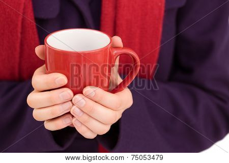 Close up of a woman in warm clothing holding mug on white background
