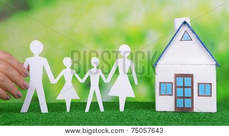 Woman hand holding paper family and house on grass on bright background