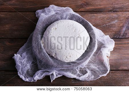 Cottage cheese on gauze in colander on wooden background