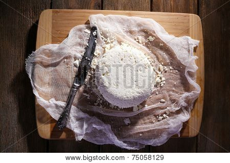 Cottage cheese and metal knife on gauze on cutting board on wooden background