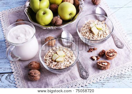 Oatmeal in bowls, walnuts, apples and yogurt on napkin on blue wooden background