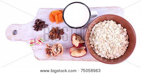 Bowl of oatmeal, mug of yogurt, dried apricots and walnuts on wooden cutting board isolated on white