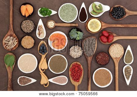 Body building and super health food selection with supplement powders in bowls and spoons over lokta paper background.