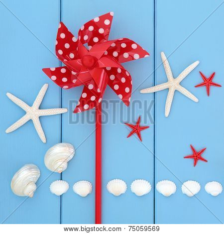 Toy windmill, starfish , cockle and mother of pearl shells over wooden blue background.