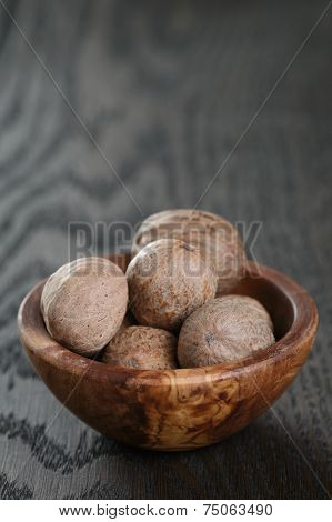 Whole Nutmegs In Olive Bowl On Oak Table