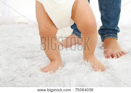 Cute baby boy taking first steps with mother in room