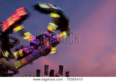 Colorful Lights Of Carnival Ride Motion Blur At Dusk